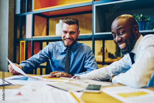 Fotografía Cheerful multiracial male employees in formal wear joking and having fun during working process in office, prosperous skilled economists overjoyed with accomplished report for business plan together