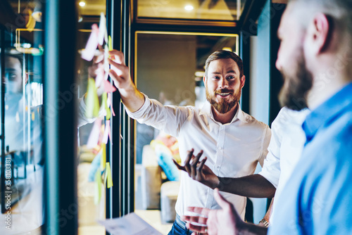 Fotografiet Cheerful bearded proud ceo in white shirt laughing while pointing on glass wall with colorful stickers and discussing solution with colleagues
