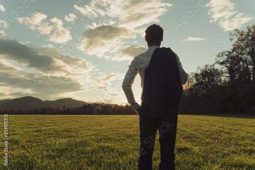 Obraz na plátně Young businessman standing in autumn meadow gazing into the future