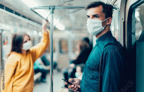 Fotografia young man in a protective mask looking at the screen of his smartphone