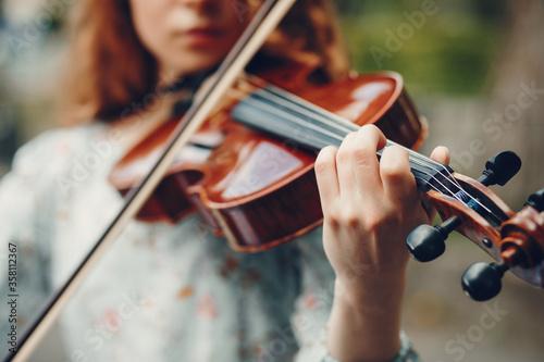 Obraz na plátně Girl in a summer park. Lady with a violin. Girl in a summer dress