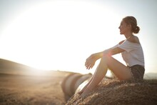 Sun Shining Over A Blonde Woman Sitting On A Stack Of Dry Grass