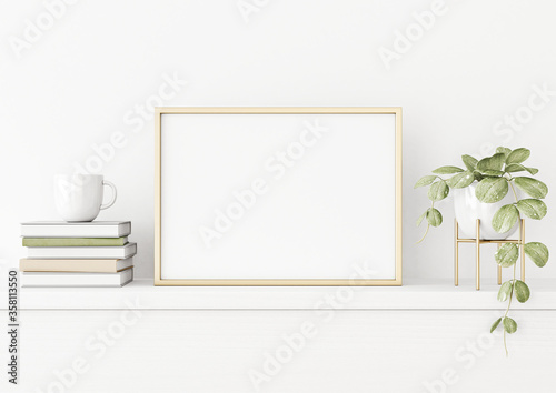 Fotografiet Poster mockup with horizontal gold metal frame on the table with green plant in pot, books, cup and trendy interior decoration on empty white wall background