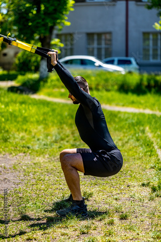 Young attractiveman does suspension training with fitness straps outdoors in the nature Fototapet