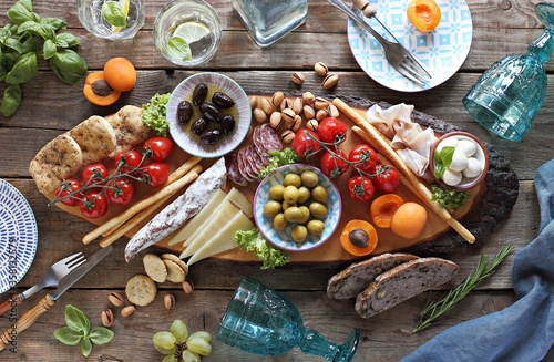 Fototapeta Mediterranean appetizers platter. Diner table with antipasto selection: cured meat and salami, gazpacho soup, jamon, olives, cheese, hummus and vegetables.   Overhead view. obraz