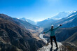 A woman wearing a beanie and blue jumper, spreads her arms wide, breathing deeply the fresh mountain air. Freedom and happiness. Below Manang valley stretches in Himalayas, along Annapurna Circuit.