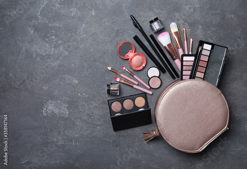 Cosmetic bag with makeup products and beauty accessories on grey stone background, flat lay Canvas-taulu