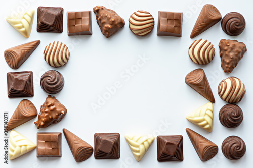 chocolate candies frame on white background, copy space, world chocolate day con Canvas Print