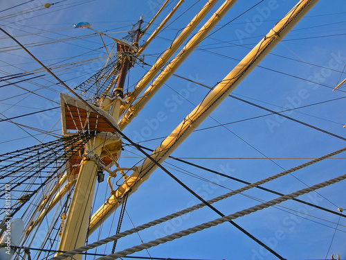 Masts of a sailing ship seen from below against the blue sky © gsphotography