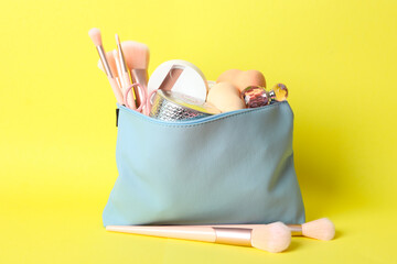 Cosmetic bag with makeup products and beauty accessories on yellow background
