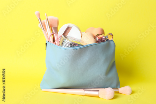 Cosmetic bag with makeup products and beauty accessories on yellow background - 358167506