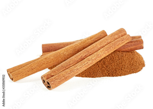 Cuadros en Lienzo Heap of ground cinnamon and cinnamon sticks isolated on a white background