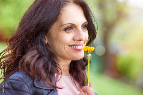 Foto Middle-age woman in black leather jacket smiling, enjoying life, smelling flower