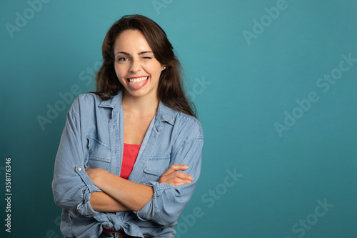 mischievous and smiling young woman with folded arms on blue background Fotobehang