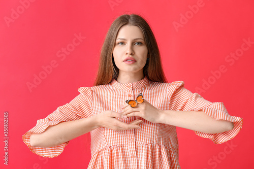 Fotografia Beautiful young woman with butterfly on color background