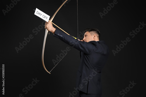 Canvas Businessman with crossbow and paper sheet with text DAY OFF on dark background