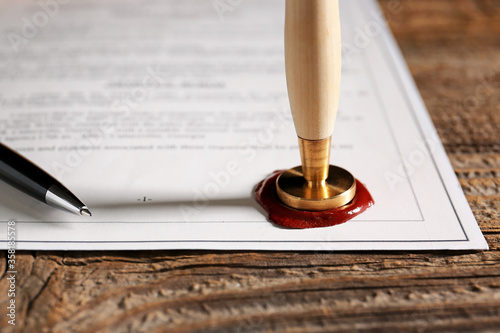 Fotografija Document with notary public wax seal on table, closeup