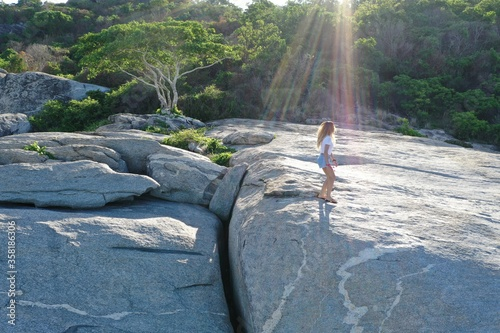 A girl stands atop large rocks near the coast Canvas Print