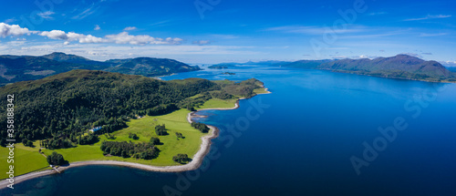 Fototapeta aerial image of loch linnhe on the west coast of the argyll and lochaber region of scotland near kentallen and duror showing calm blue waters and clear skies with green forest coast line obraz