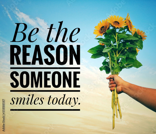 Obraz Inspirational quote - Be the reason someone smiles today. With a hand holding a bunch of sunflowers against bright blue sky background. Motivational text message with flowers and sky background. - fototapety do salonu