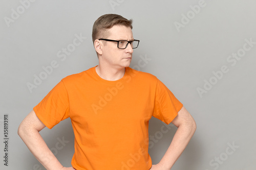 Portrait of serious mature man with glasses, wearing orange T-shirt Fototapet