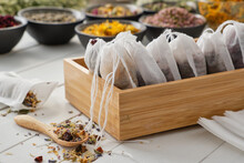 Wooden Box Of Tea Bags Filled With Dry Medicinal Herbs And Flowers. Bowls Of Medicinal Plants On Background. Alternative Medicine