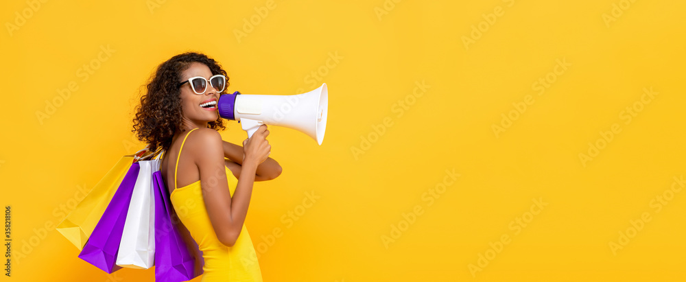 Fototapeta Happy beautiful woman with shopping bags and megaphone on isolated colorful yellow banner background for sale and discount concepts