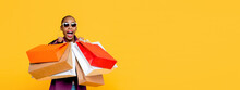 Beautiful Fashionable African American Woman With Colorful Shopping Bags In Surprised Sale Concept Isolated On Yellow Banner Background
