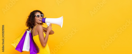 Fototapeta Happy beautiful woman with shopping bags and megaphone on isolated colorful yellow banner background for sale and discount concepts obraz