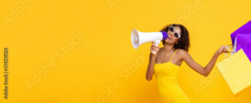 Photo Happy beautiful woman with shopping bags and megaphone on isolated colorful yell