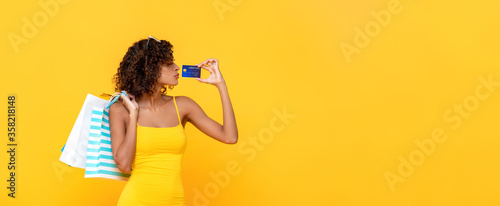 Fotografia Fashionable curly hair woman carrying shopping bags holding credit card on yello