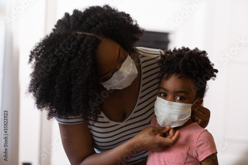 Fotografía African American mother helping her daughter put on a face mask.