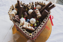 Sweet Heart-shaped Chocolate Birthday Cake With Sweets On Top As Decoration, Made Up Of Chocolate Filled Tubes