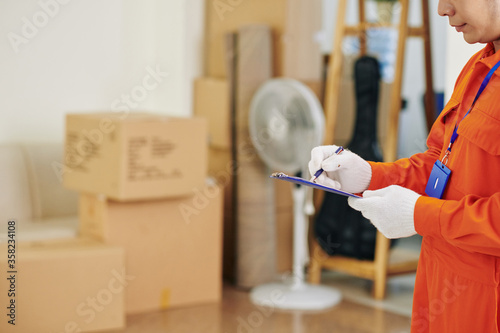 Fototapeta Horizontal side view shot of unrecognizable moving service worker making notes in papers, copy space obraz