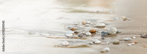 Canvas Print A close up view of smooth polished multicolored stones washed ashore on the beach