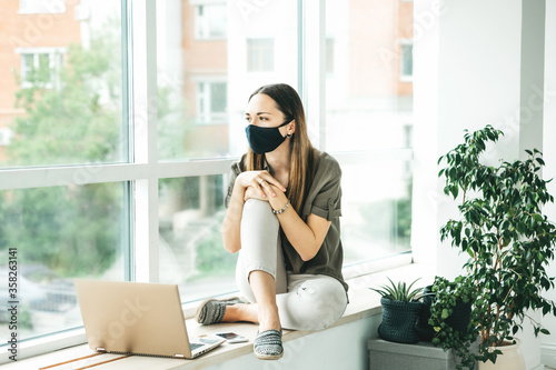 Girl with face mask and laptop. Wallpaper Mural
