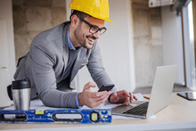Young Smiling Architect In Suit With Helmet On Head Holding Smart Phone And Using Laptop While Leaning On Table In Building In Construction Process.