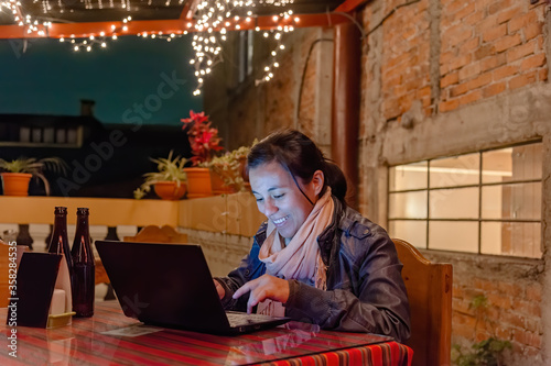фотография Woman is working smiling with a laptop on a hotel terrace at night lit by Christ