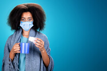 Black Woman In Medical Mask With A Cup In Her Hand On A Blue Background In The Studio