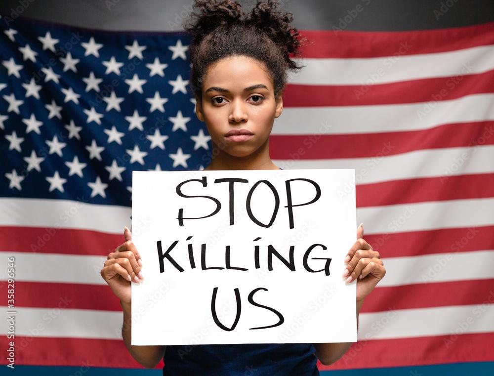 Fototapeta Black woman holding placard STOP KILLING US