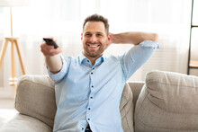 Happy Guy Watching TV At Home, Holding Remote Control