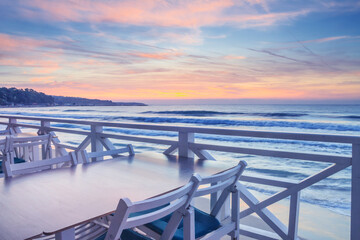 Seaside landscape - the cafe on the embankment with views of the sunrise over the sea, city of Varna, on the Black Sea coast of Bulgaria