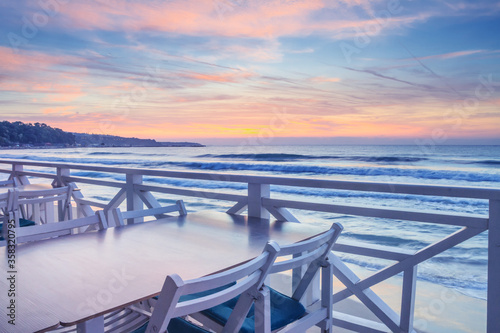 Obraz Seaside landscape - the cafe on the embankment with views of the sunrise over the sea, city of Varna, on the Black Sea coast of Bulgaria - fototapety do salonu