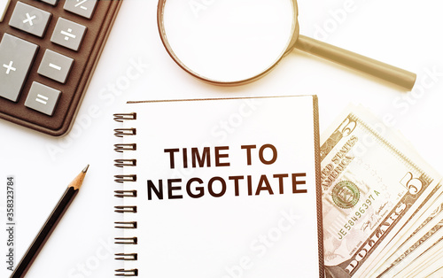 Photo Notebook with text Time To Negotiate on white table with calculator, magnifier, pencil and dollars