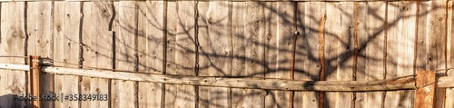 Photo Panoramic fragment of an old wooden fence with a shadow from a tree