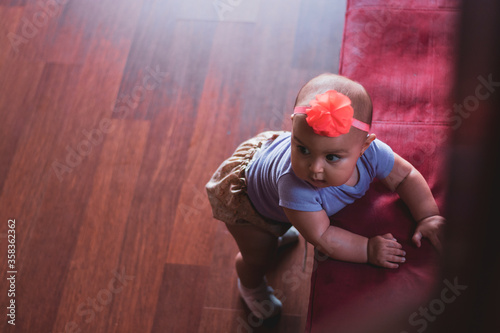 Valokuva bebé de pie en el sofá