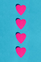 Studio Shot Of Row Of Pink Paper Hearts Against Blue Background