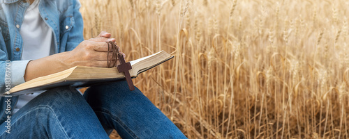 Foto Christian woman praying on holy bible and wooden cross in barley field on summer
