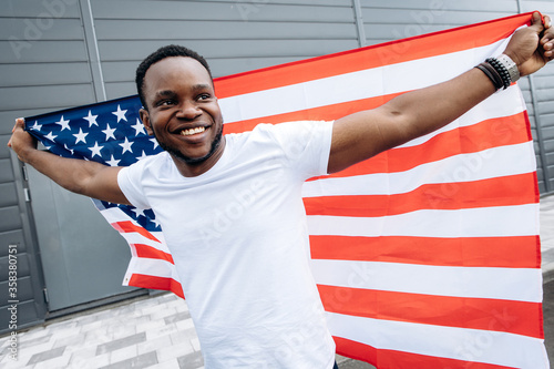 Fotografija Cheerful attractive african american guy with hands up holds flag of USA behind him and smiling, he is in a positive mood