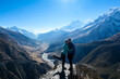 A couple standing at a mountain ledge, hugging and enjoying the view on Manang valley stretching in Himalayas, along Annapurna Circuit. Freedom. Love and passion. Snow capped Himalayas around.